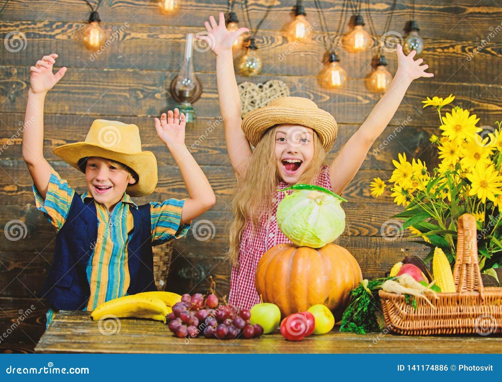 Los niños juegan el fondo de madera de las verduras El sombrero del desgaste del muchacho de la muchacha de los niños celebra est