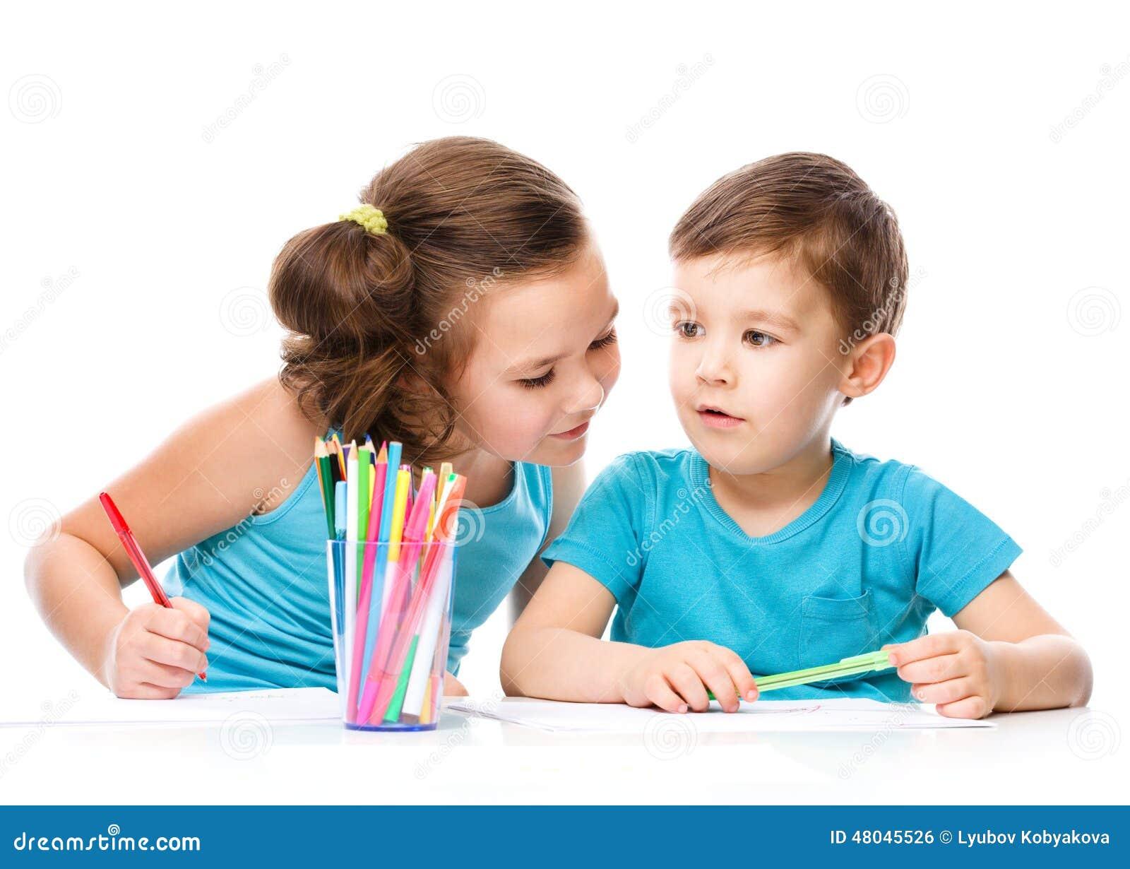 Los niños lindos están dibujando en el Libro Blanco
