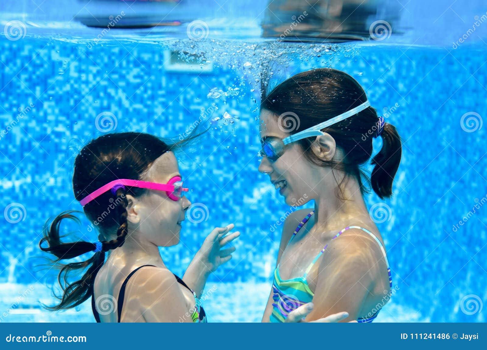 Los niños nadan en la piscina subacuática, las muchachas activas felices se divierten bajo el agua, la aptitud de los niños y dep