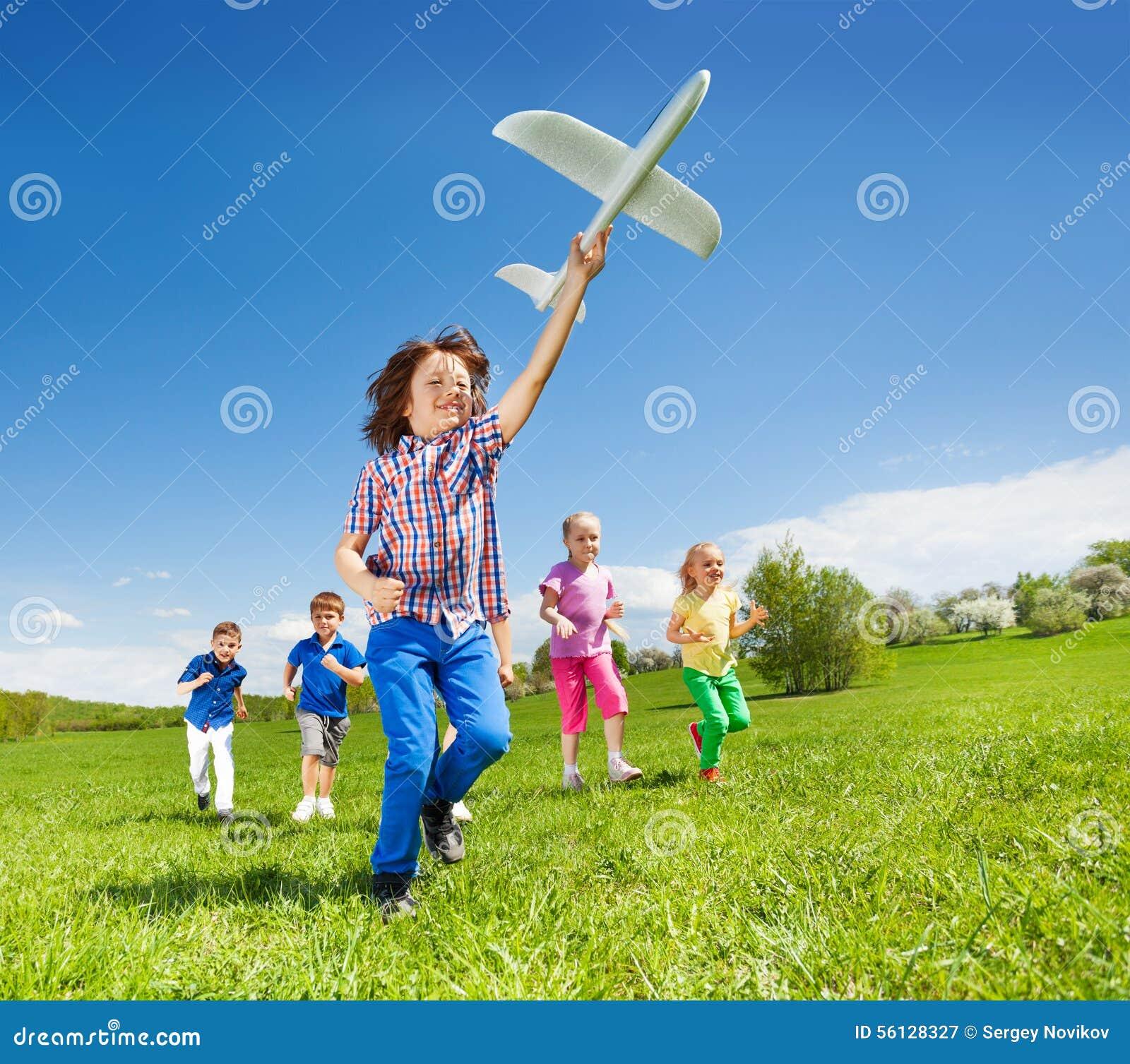 Los niños positivos y el muchacho corrientes que sostienen el aeroplano juegan