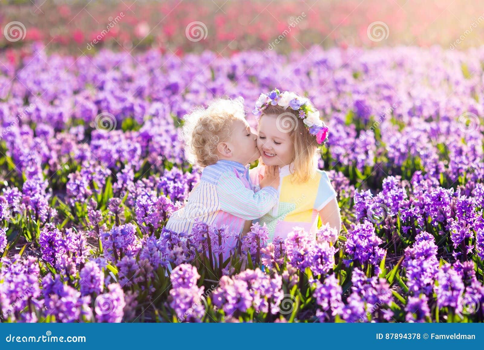 Los niños que juegan en jardín floreciente con el jacinto florecen
