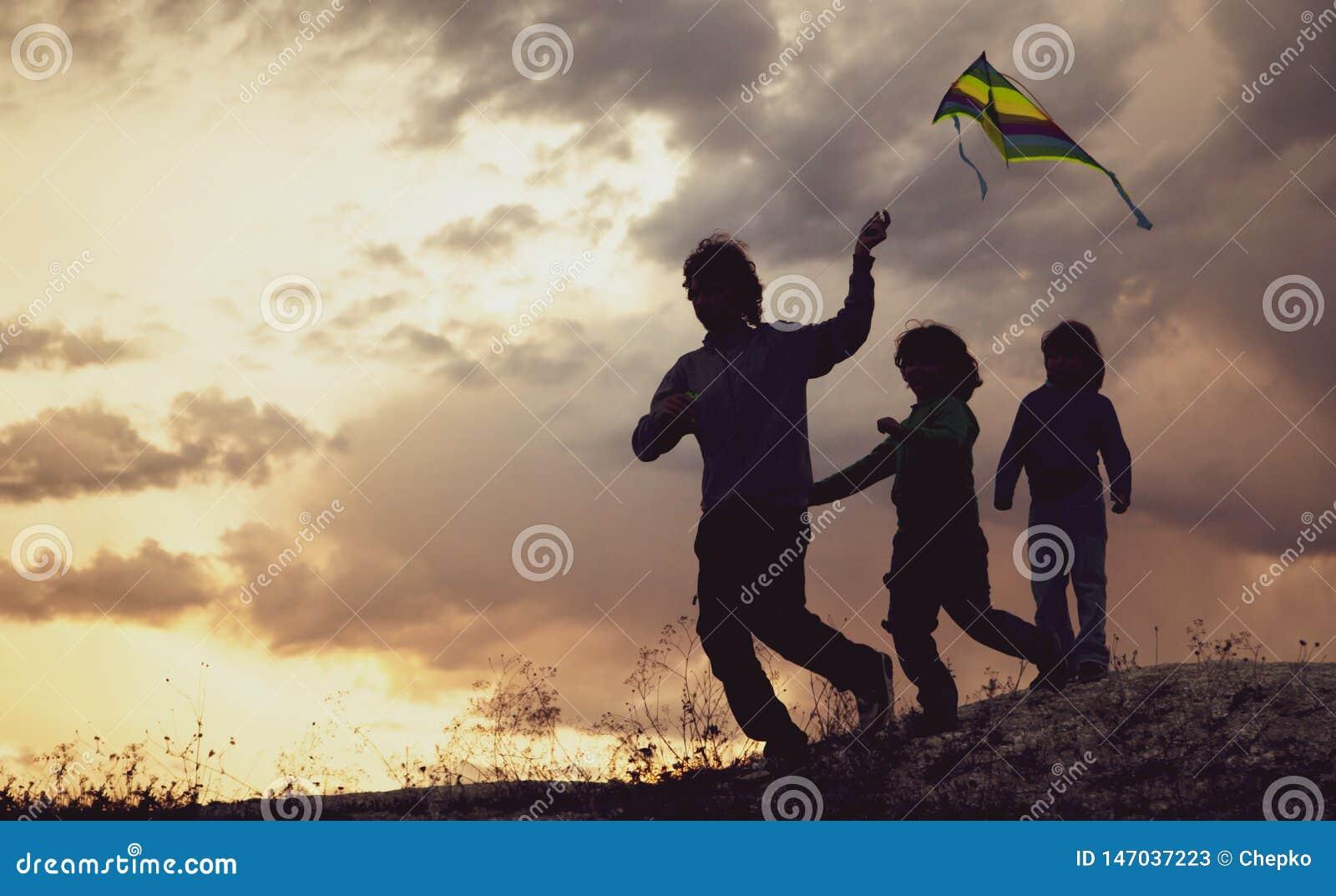 Los niños que jugaban con la cometa en prado de la puesta del sol del verano siluetearon