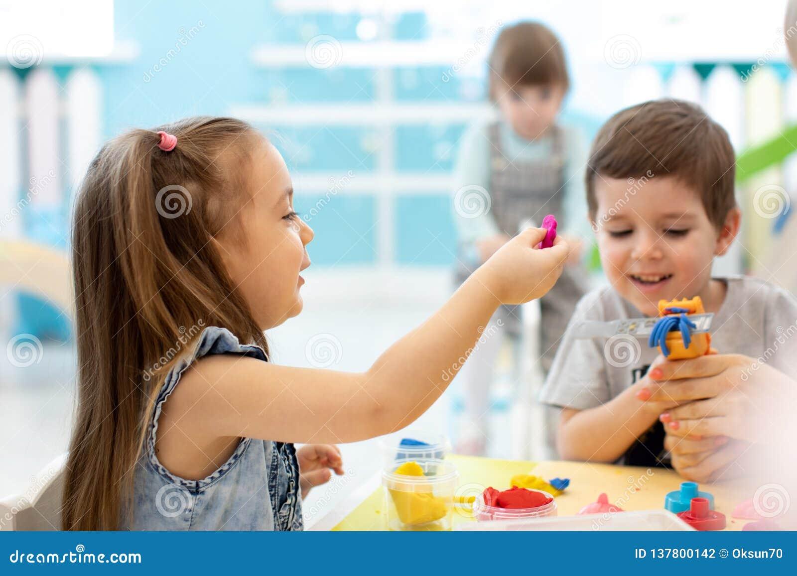 Los niños se divierten así como la arcilla de modelado colorida en la guardería Niños creativos que moldean en guardería Niños