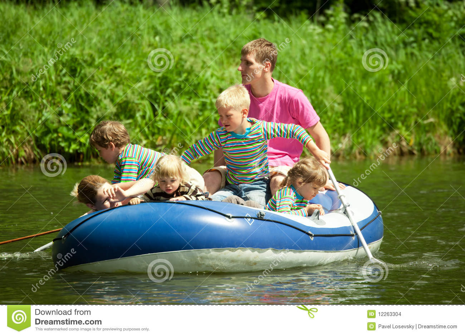 Los niños van para el mecanismo impulsor en el barco bajo supervisión