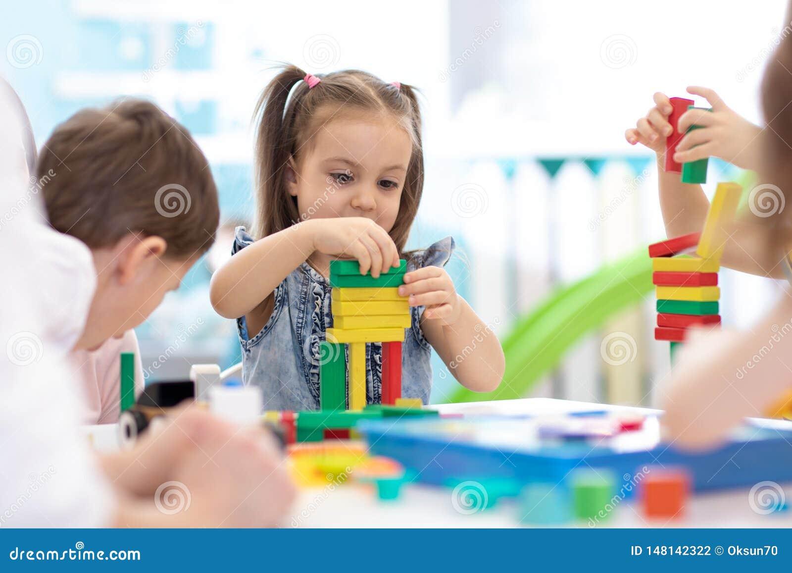 Los ni?os construyen los juguetes del bloque en casa o guarder?a Ni?os emocionales que juegan con los bloques del color Juguetes