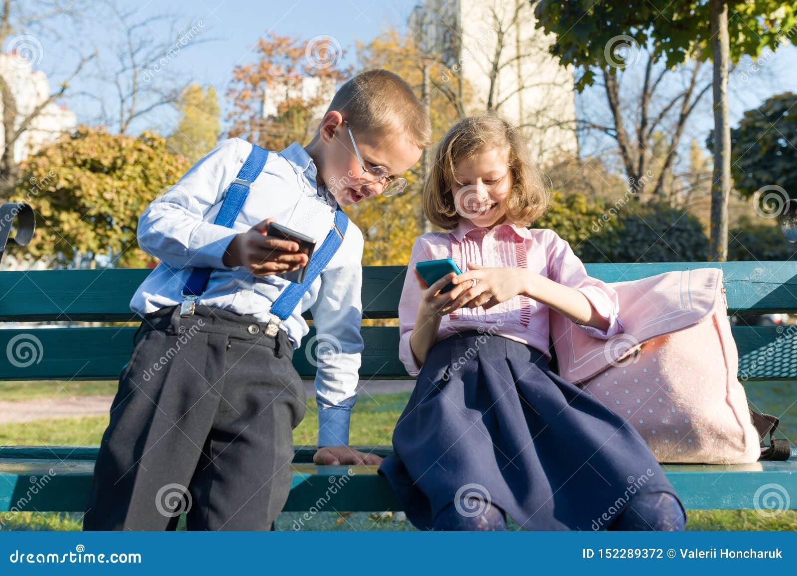 Los ni?os muchacho y muchacha de la diversi?n est?n mirando en smartphones En un banco con las mochilas de la escuela, parque sol