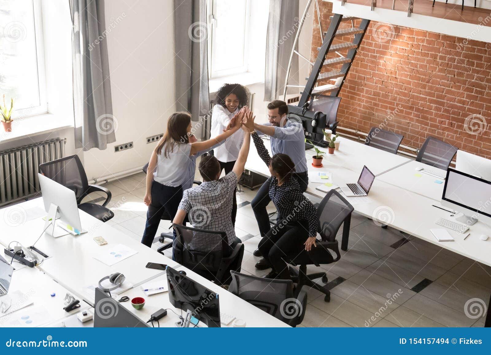 Los oficinistas multirraciales emocionados combinan dando altos cinco juntos