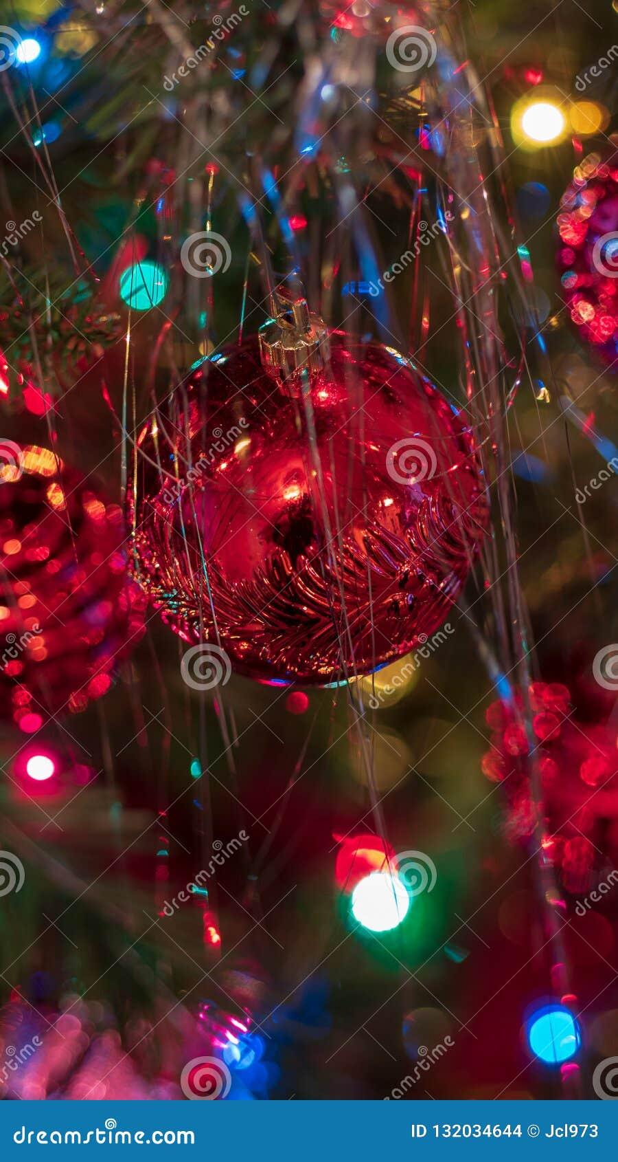 Los ornamentos brillantemente coloreados, alegres del árbol de navidad colgaron para arriba con las luces y la malla