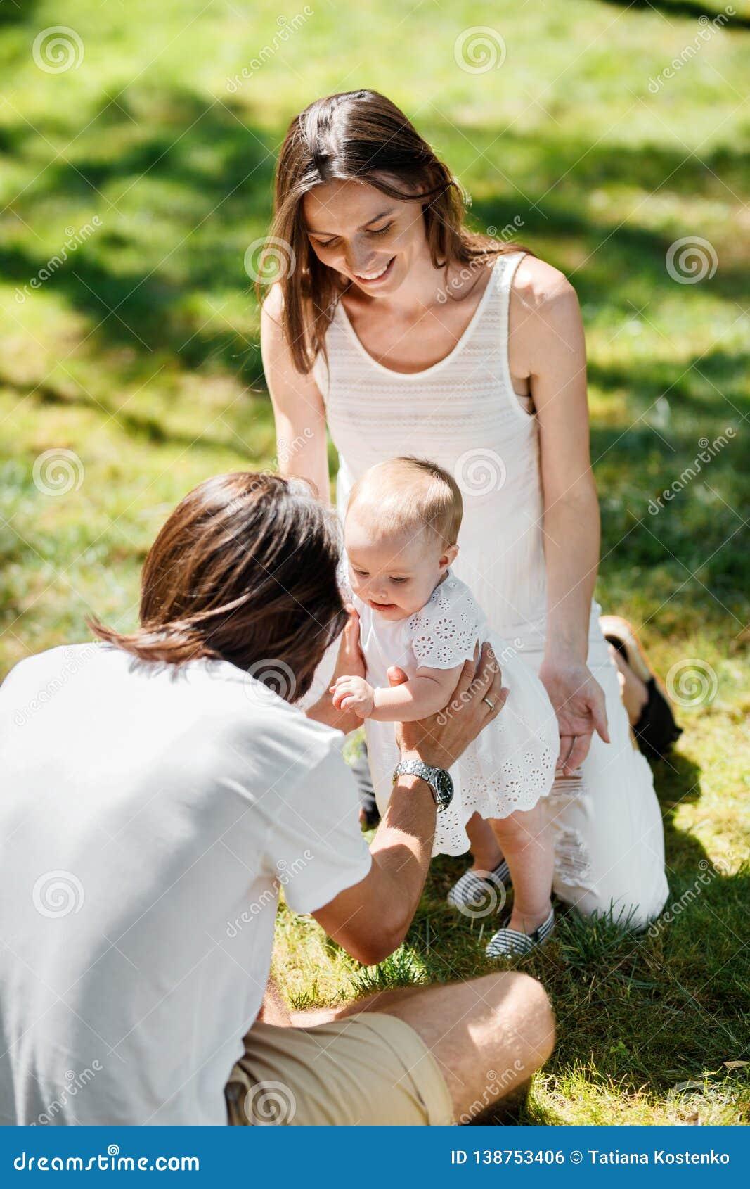 Los padres encantados se están sentando en el césped y están enseñando su pequeña hija a cómo hacer sus primeros pasos