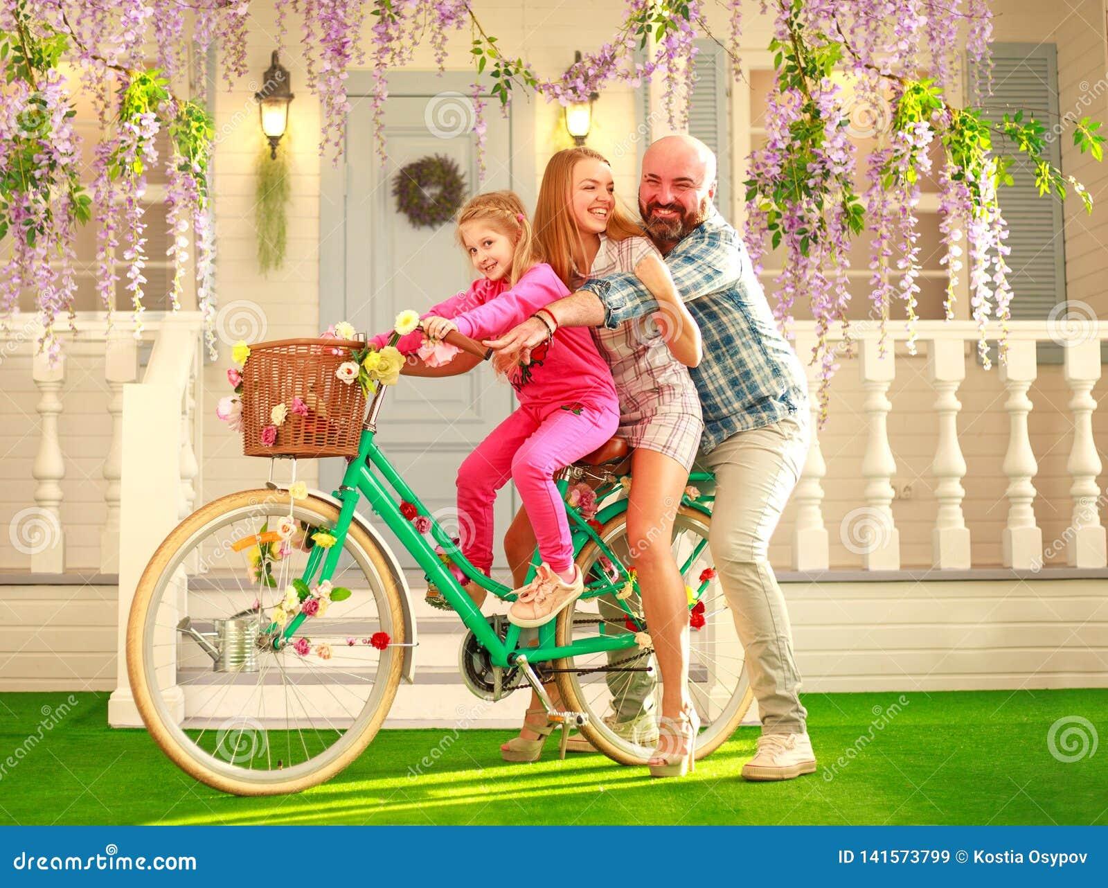 Los padres felices con un niño, hija, aprenden montar una bici, vacaciones de verano de la forma de vida de la familia en casa