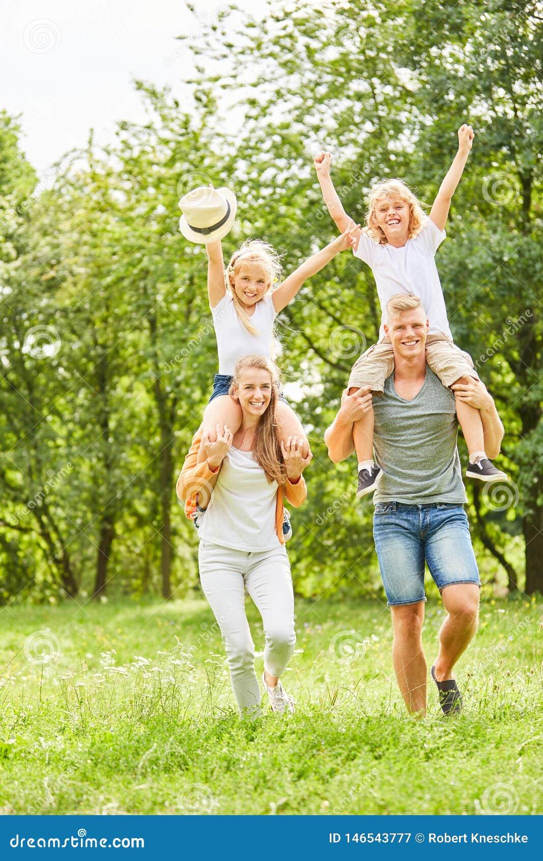 Los padres llevan a niños alegres a cuestas