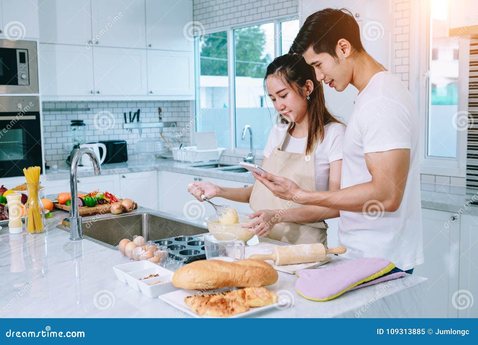 Los pares adolescentes asiáticos están ayudando a hacer la cena