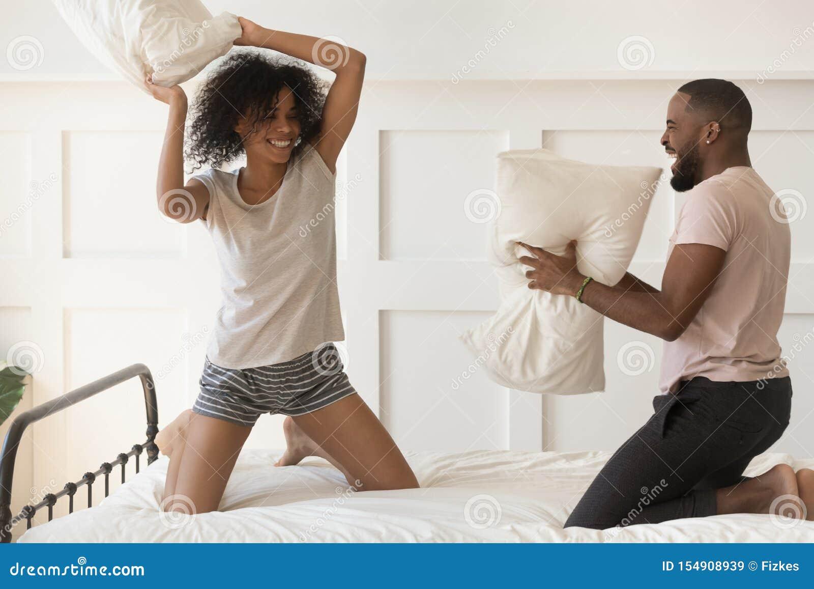 Los pares afroamericanos felices disfrutan de lucha de almohada en cama juntos