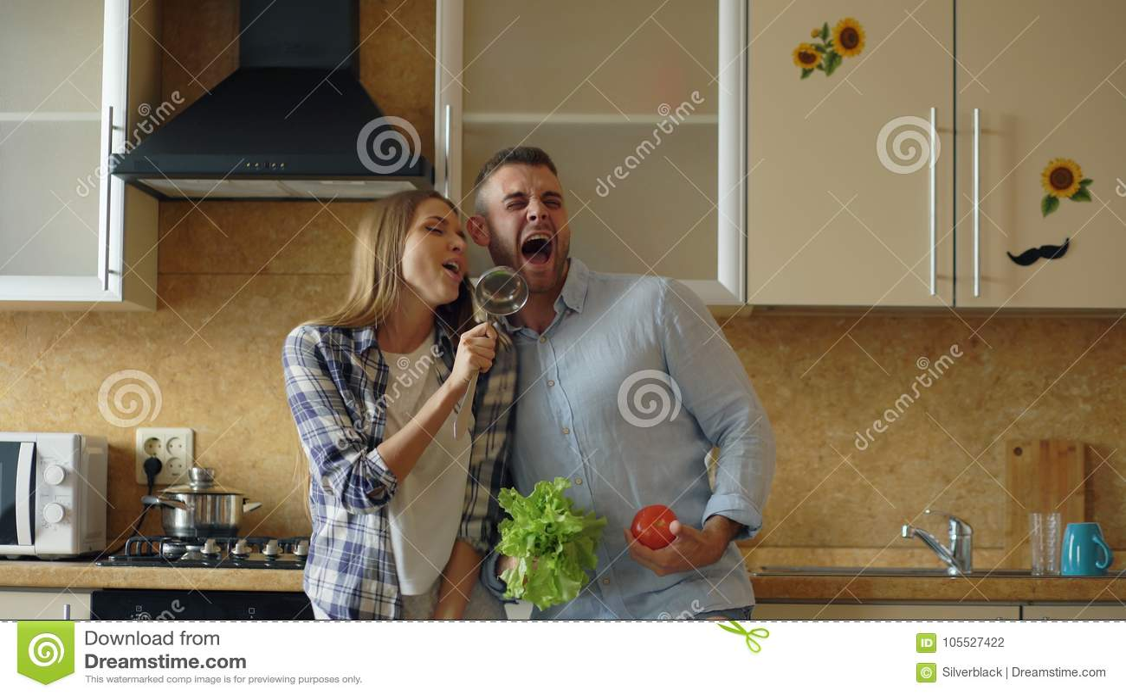 Los pares alegres jovenes atractivos tienen el baile de la diversión y canto mientras que cocinan en la cocina en casa