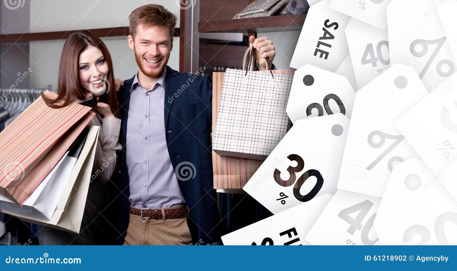 Los pares alegres muestran sus compras después de venta