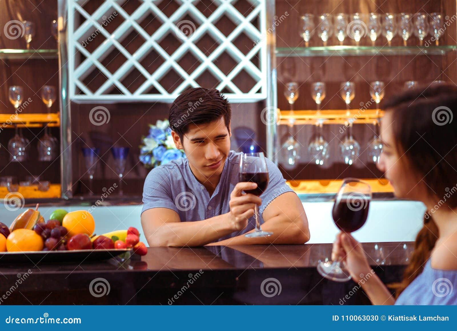 Los pares asiáticos jovenes juntos sirven y los vidrios del tintineo de la mujer