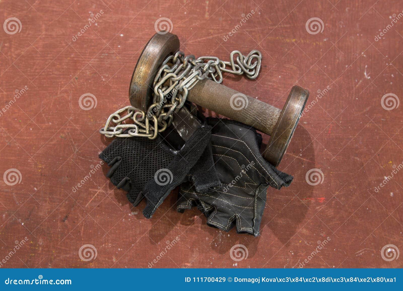 Los pares de aptitud ennegrecen guantes con la cadena de plata y pequeña pesa de gimnasia usada contra el fondo rojo, anaranjado,