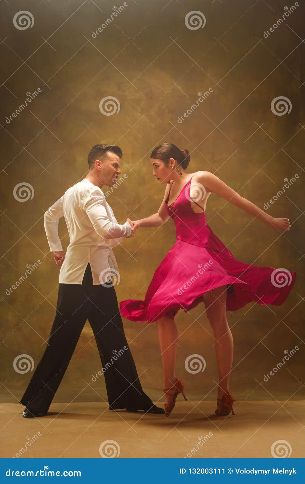 Los pares del salón de baile de la danza en oro visten el baile en fondo del estudio