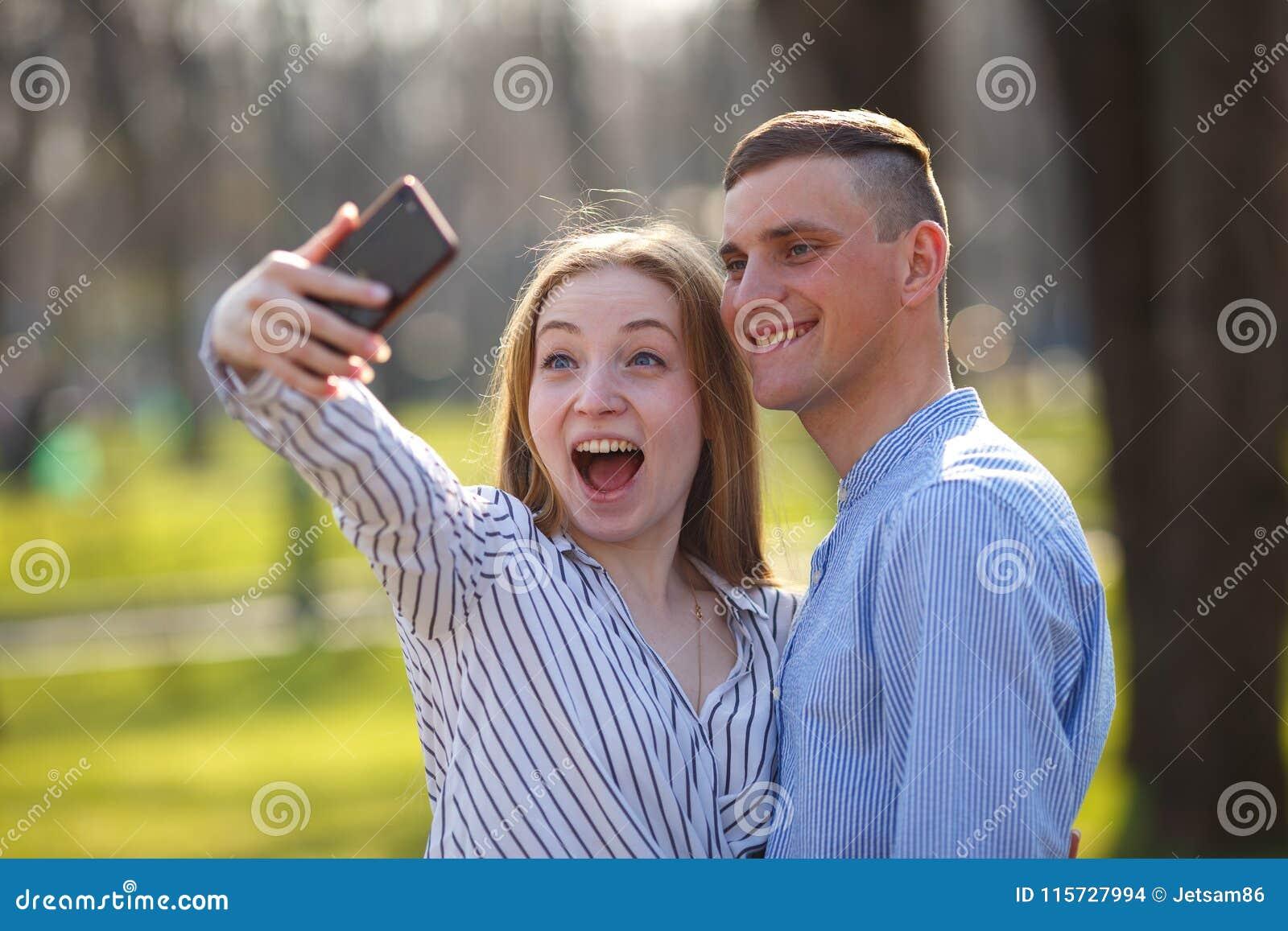 Los pares descuidados de los jóvenes en el amor que camina al aire libre juntos gozan de DA