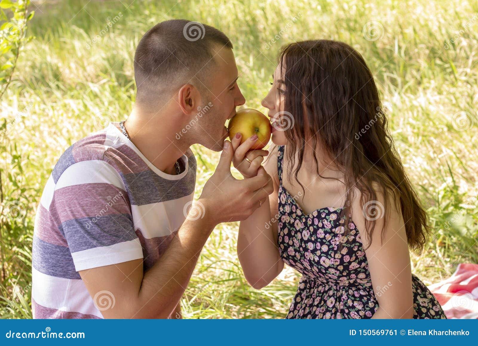 Los pares en muchacho y muchacha del amor comen aire libre de la comida campestre del verano de la manzana