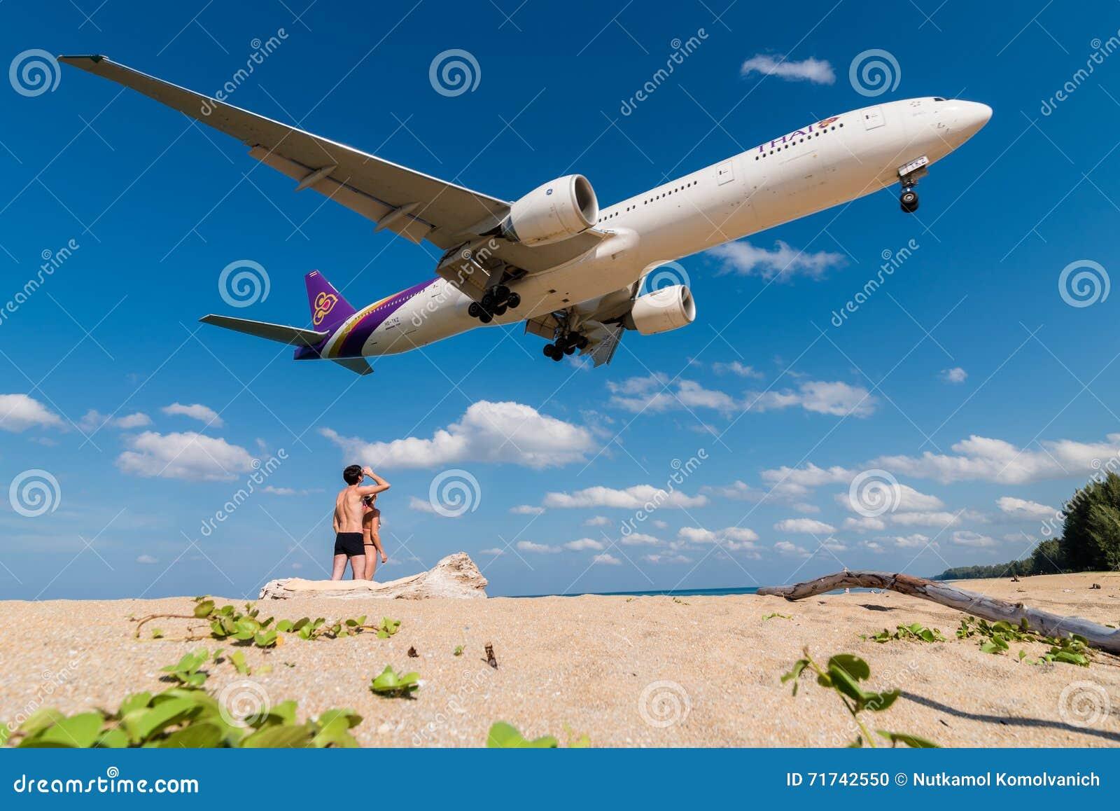 Los pares están mirando el aeroplano de Thai Airways, Boeing 777, aterrizando