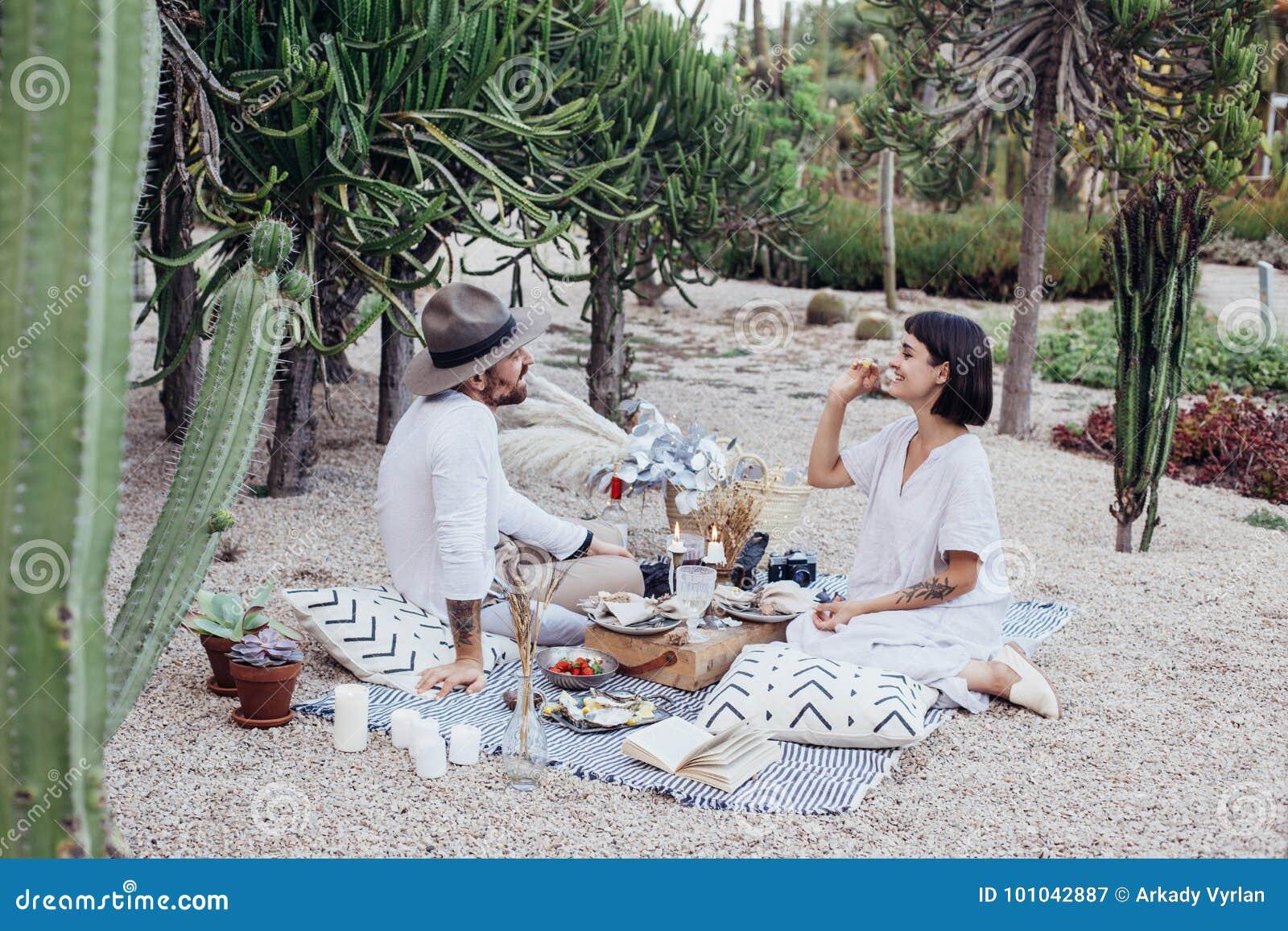 Los pares fecha romántica ponen en la manta de la comida campestre