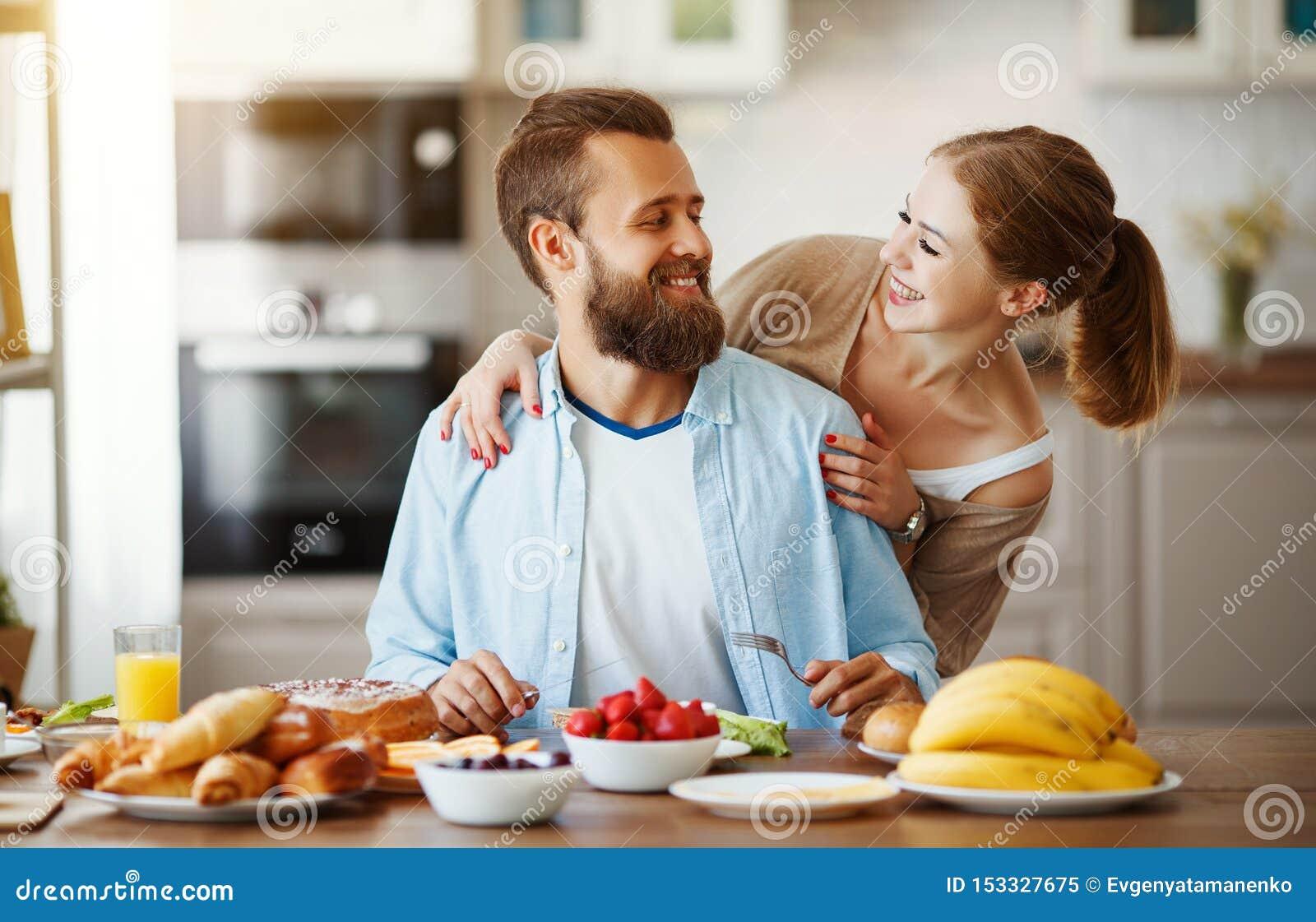 Los pares felices de la familia desayunan en cocina por mañana
