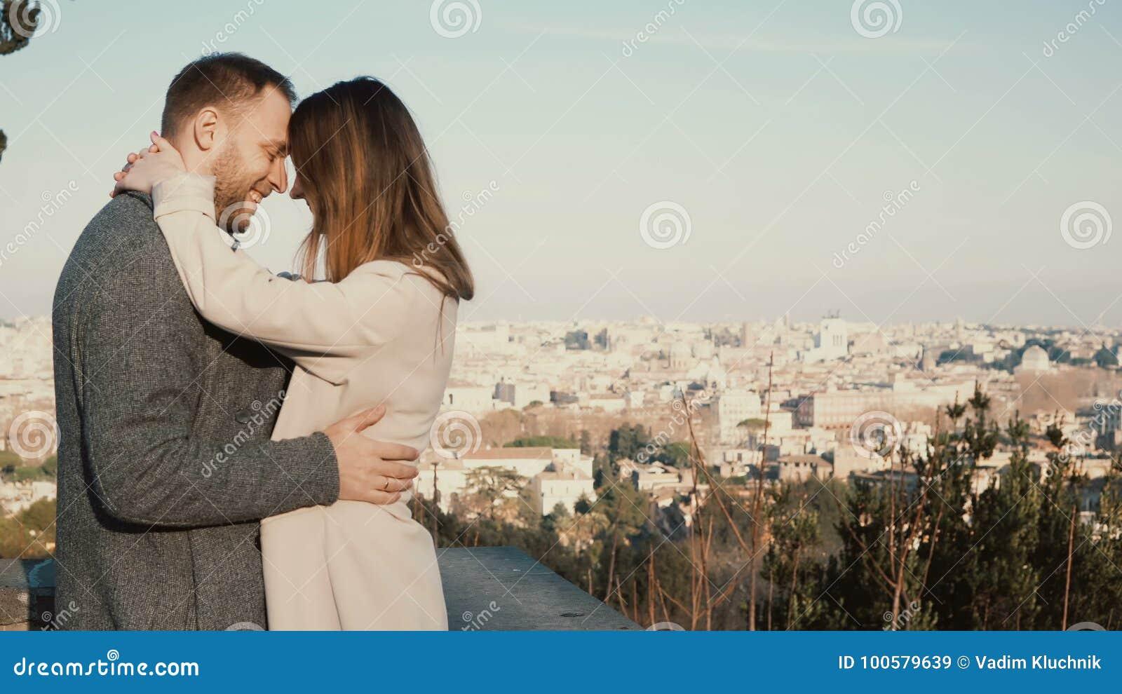 Los pares hermosos jovenes abrazan y beso contra el panorama de Roma, Italia Fecha romántica del hombre y de la mujer felices