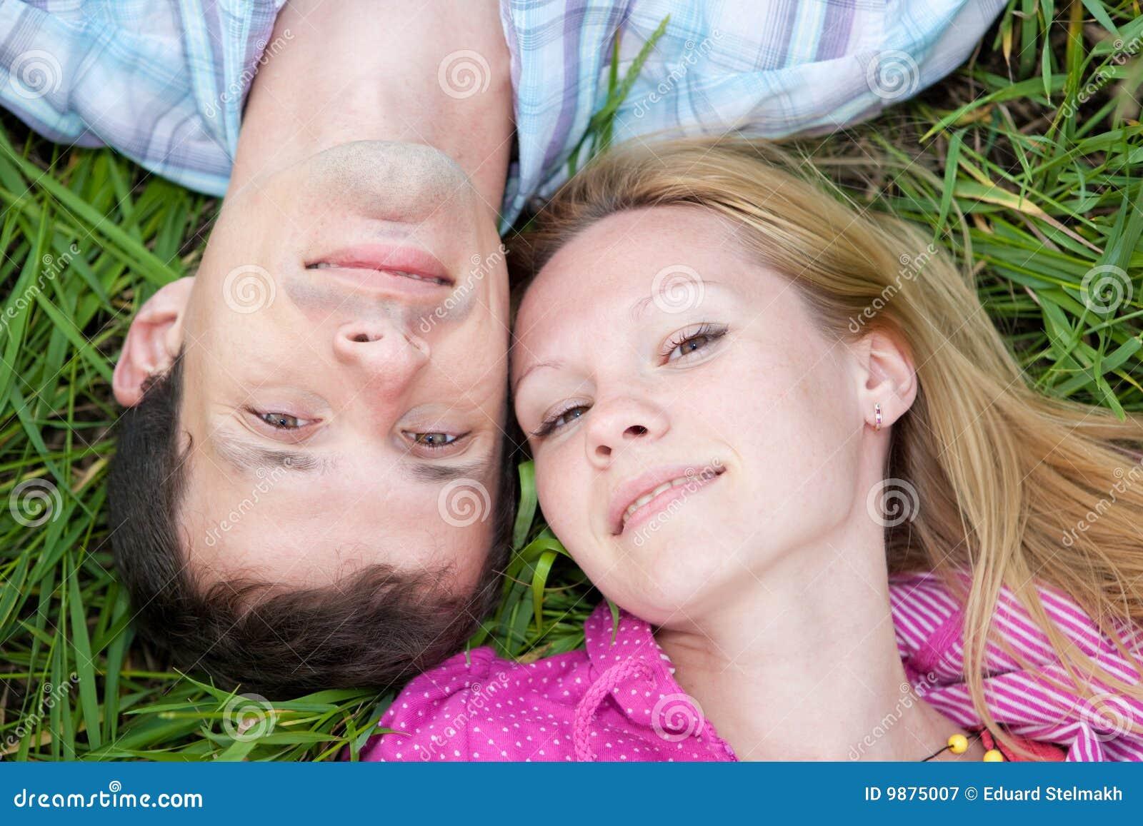 Los pares jovenes del amor ponen en la hierba verde al aire libre.