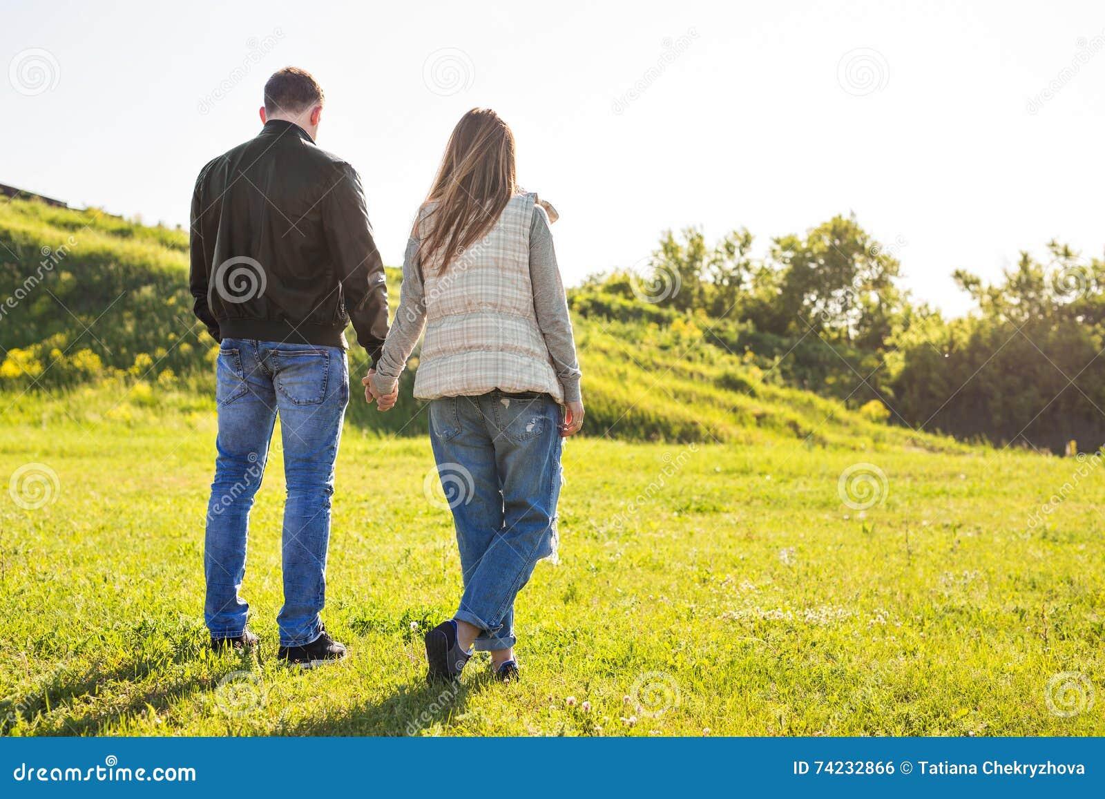 Los pares jovenes en el amor que camina en el otoño parquean llevar a cabo las manos que miran en la puesta del sol