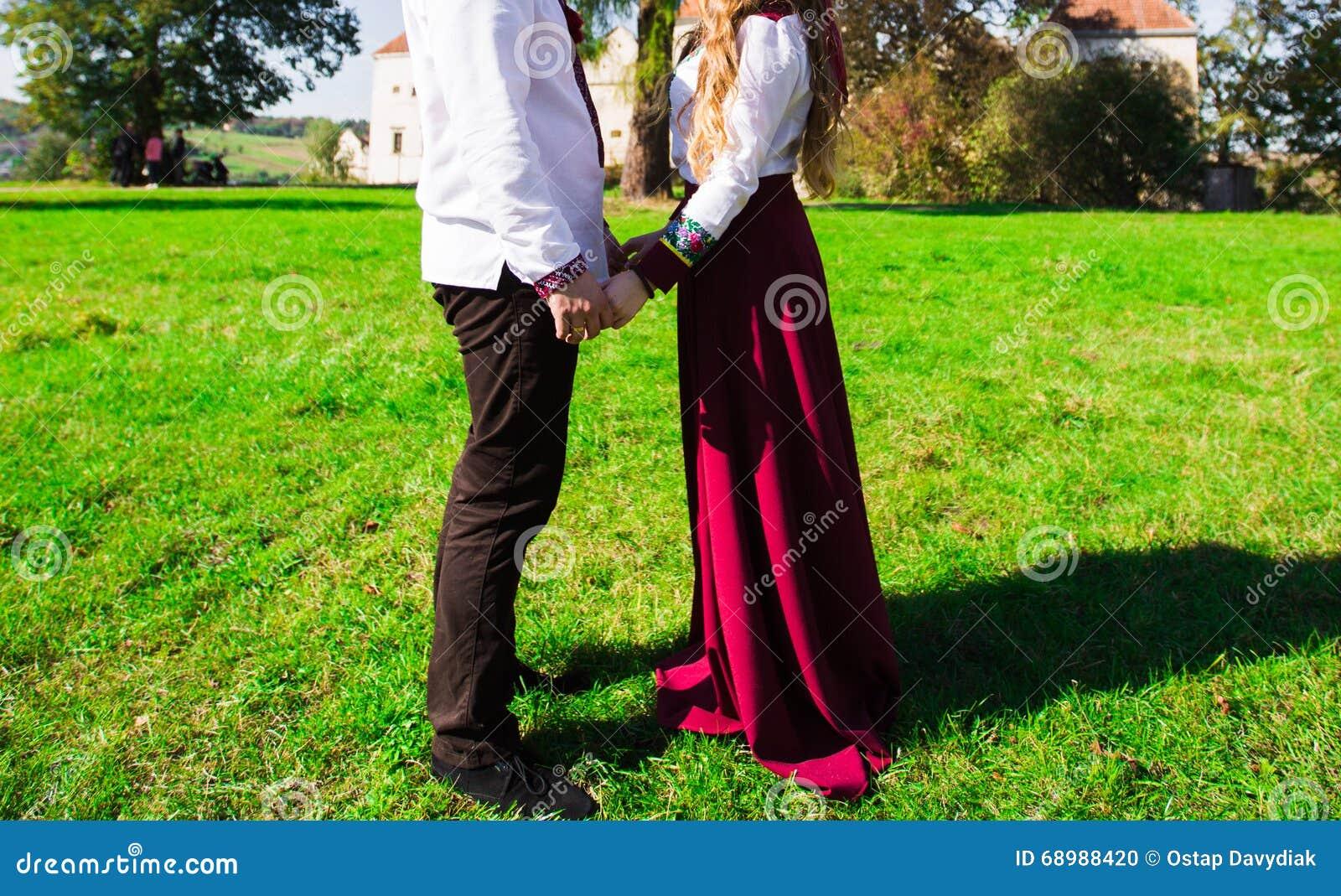 Los pares jovenes en el amor que camina en el otoño parquean sostener lo de las manos