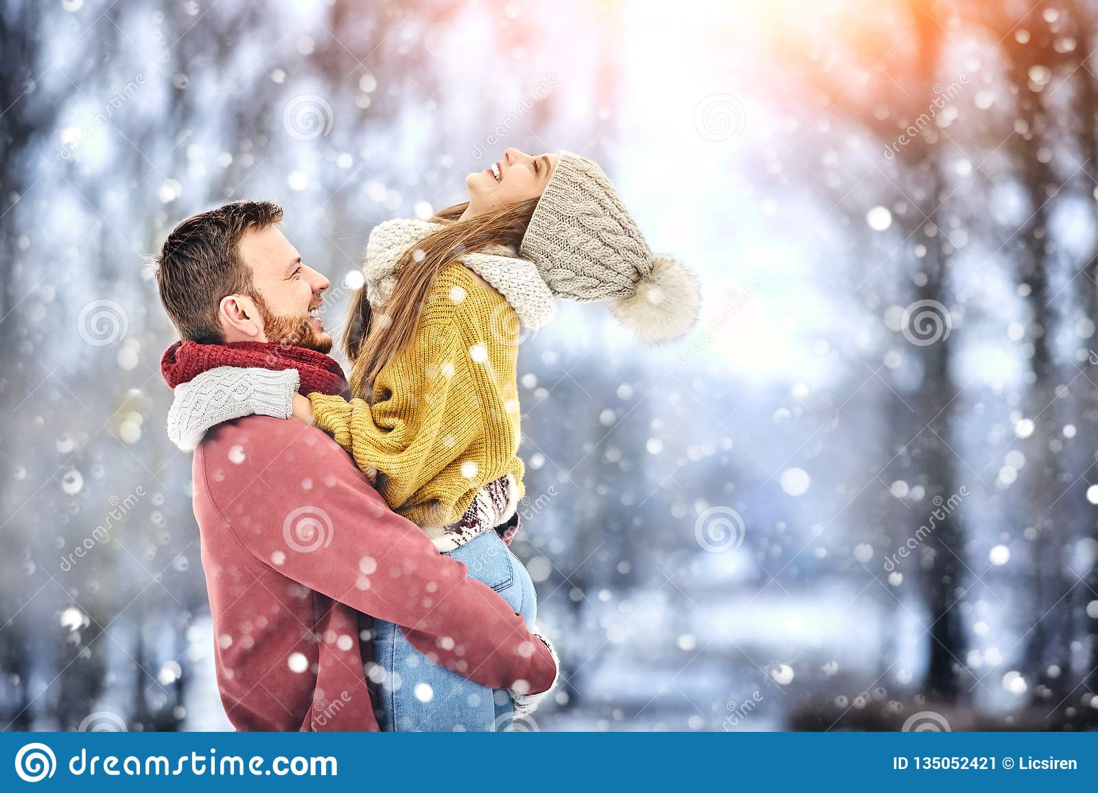 Los pares jovenes felices en invierno parquean la risa y divertirse Familia al aire libre