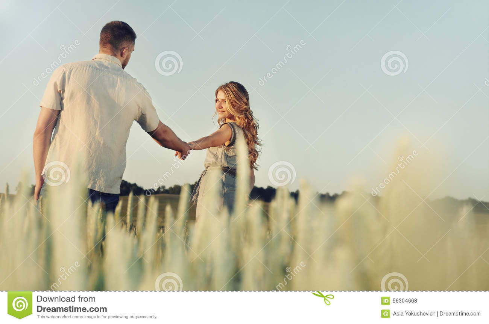 Los pares jovenes felices imponentes en el amor que presenta en verano colocan holdi