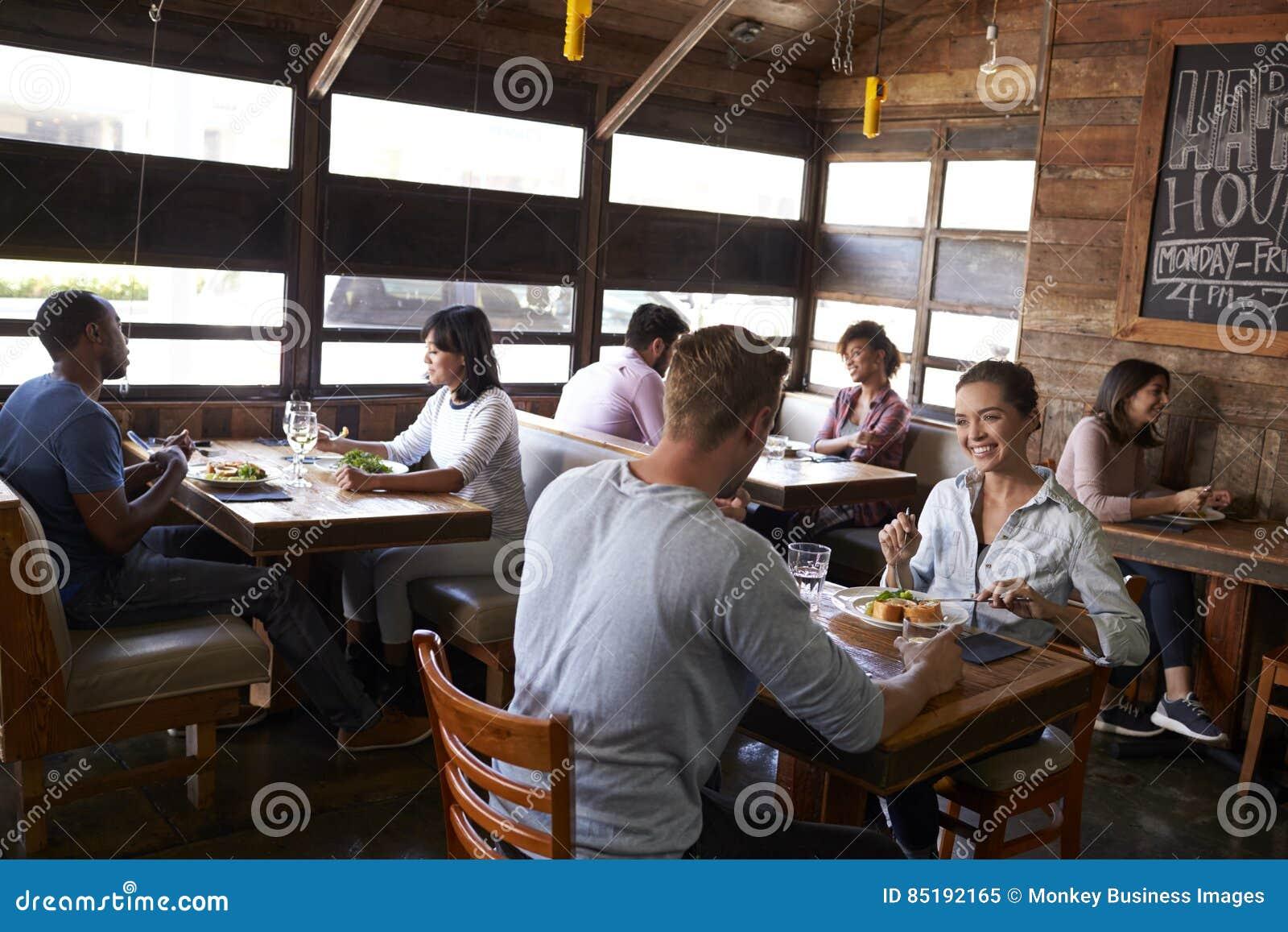 Los pares jovenes que comen el almuerzo se relajan en un restaurante