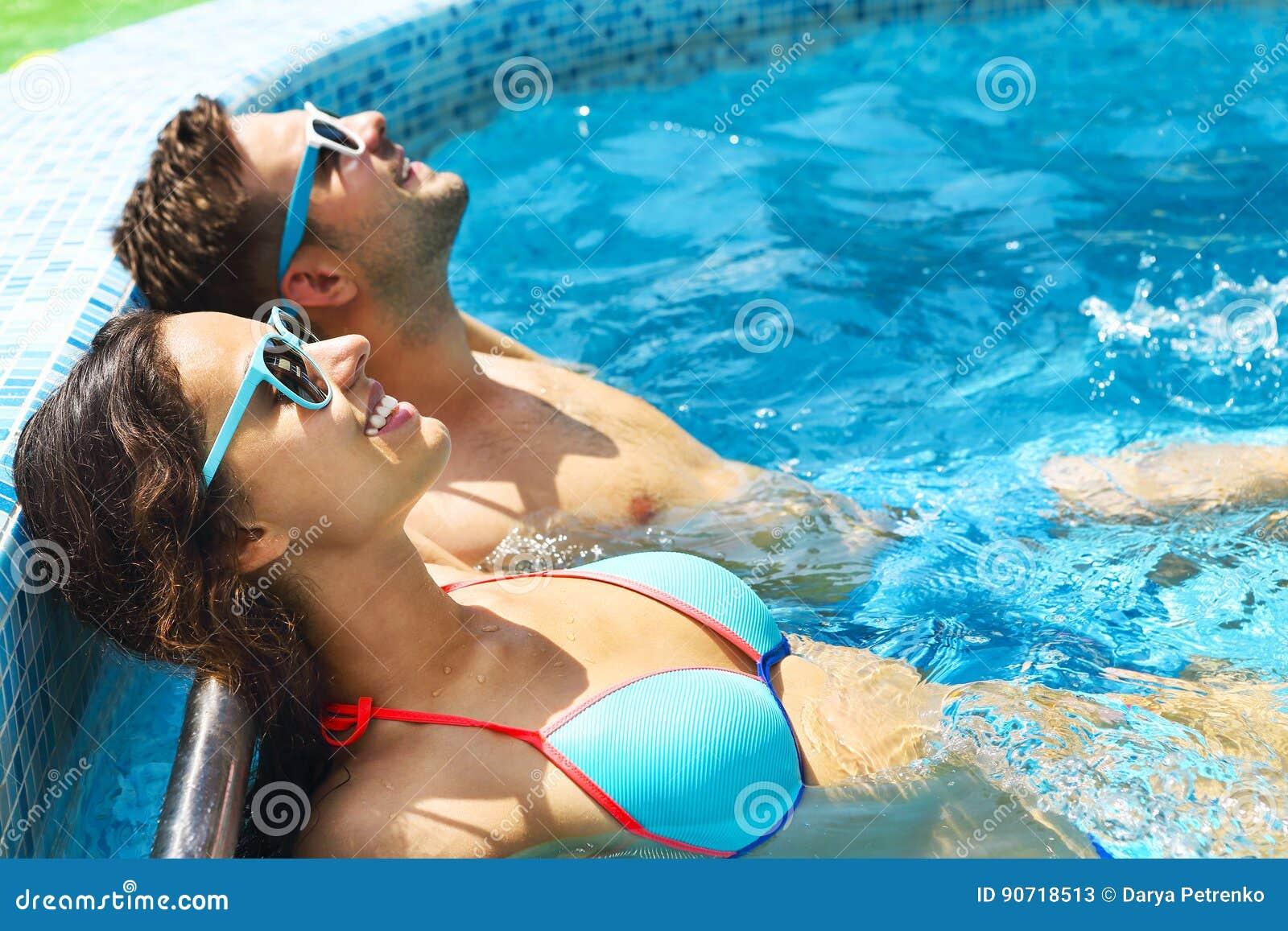 Los pares jovenes son relajantes en piscina
