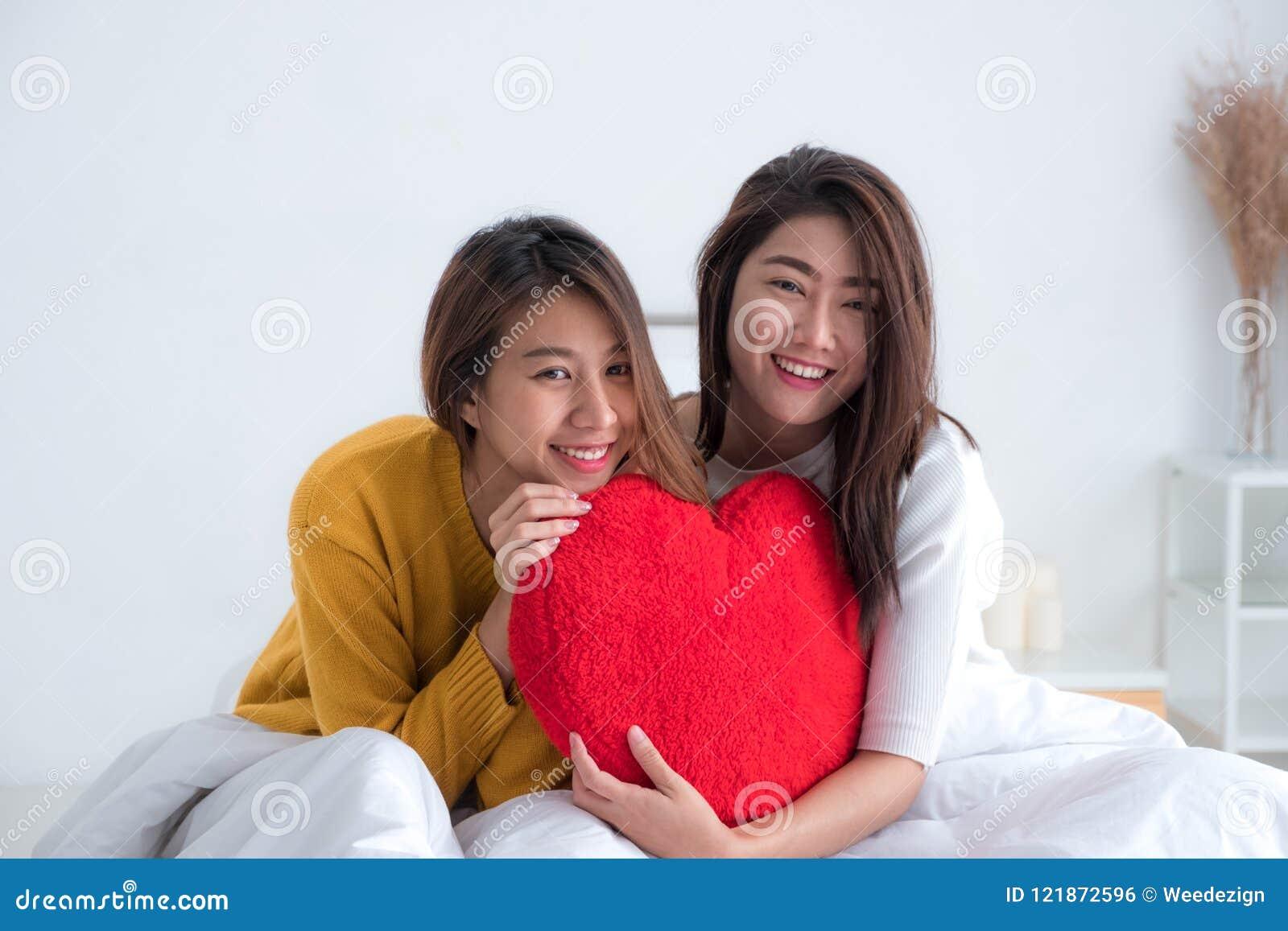 Los pares lesbianos del lgbt de Asia que llevan a cabo el corazón rojo soportan juntos y s
