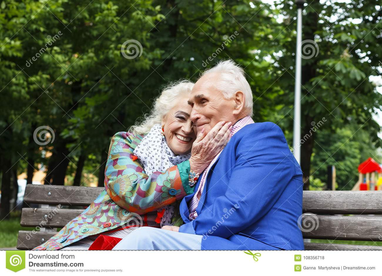 Los pares mayores de la familia que hablan en un banco en una ciudad parquean El fechar feliz de los mayores