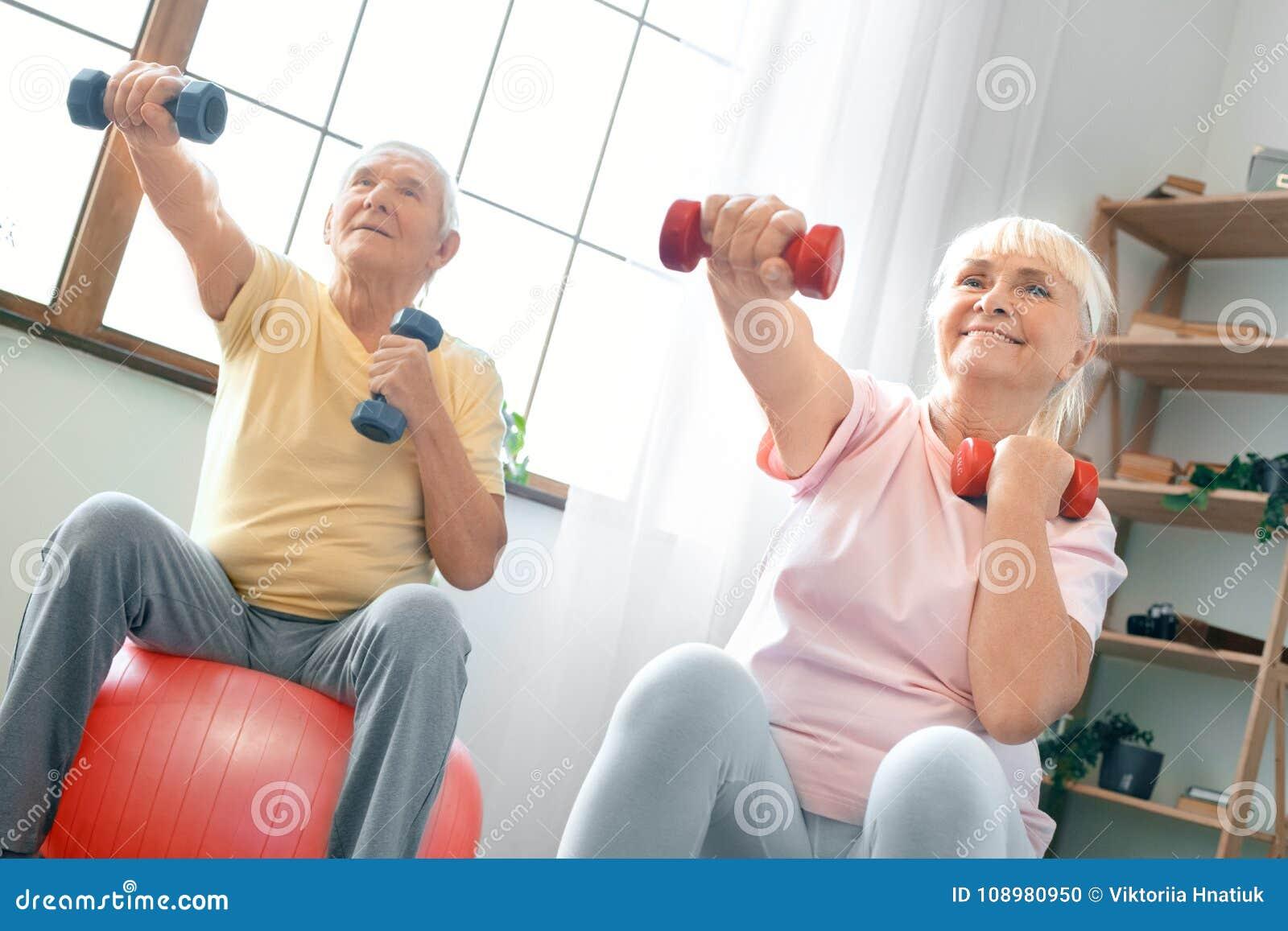 Los pares mayores ejercitan juntos en casa haciendo aeróbicos con los dubbells en frente