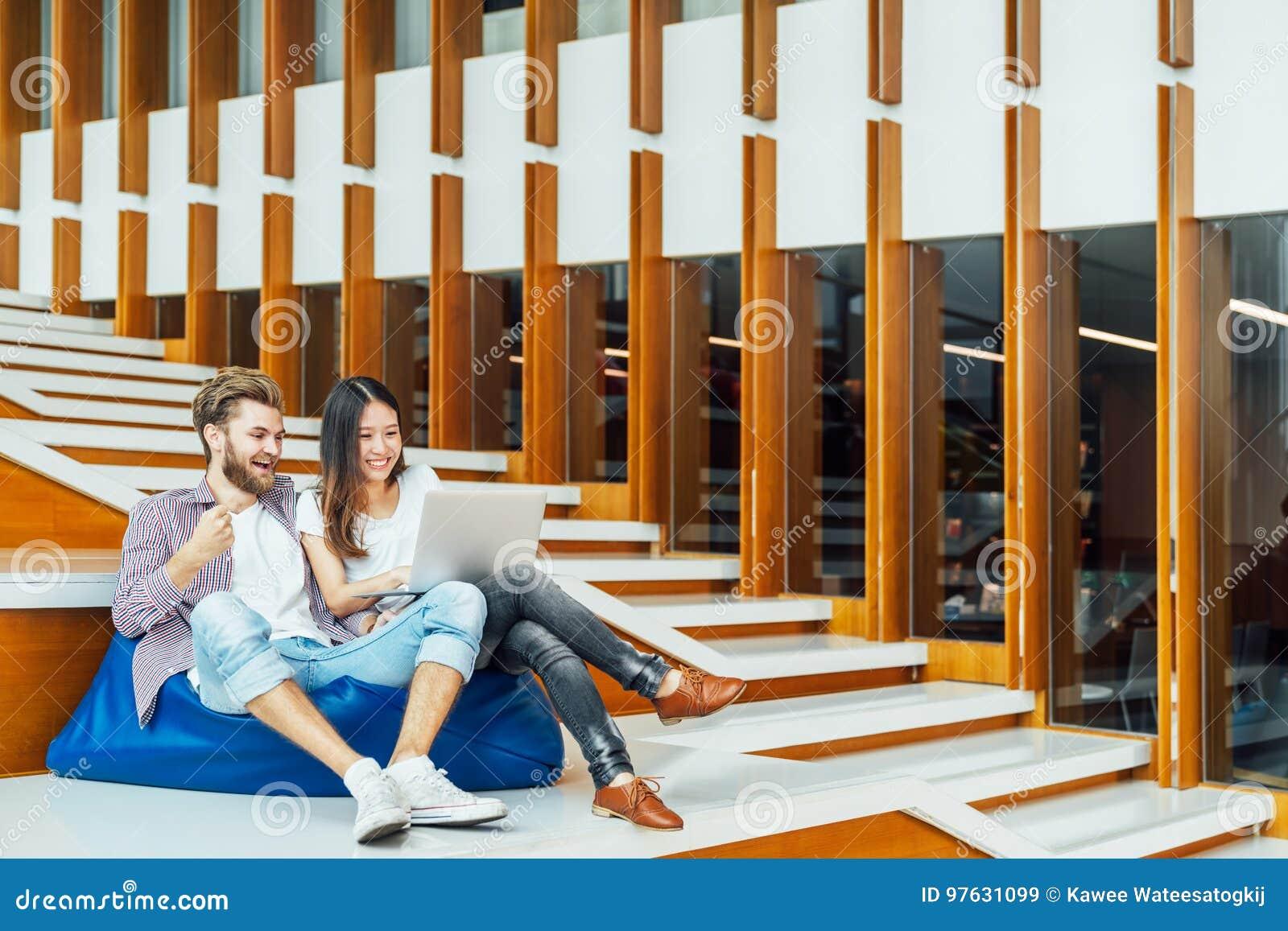 Los pares Multi-étnicos del estudiante universitario celebran así como el ordenador portátil en las escaleras en campus universit