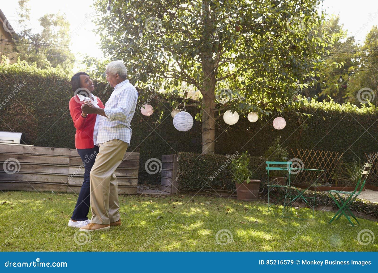 Los pares negros mayores bailan en su jardín trasero, integral