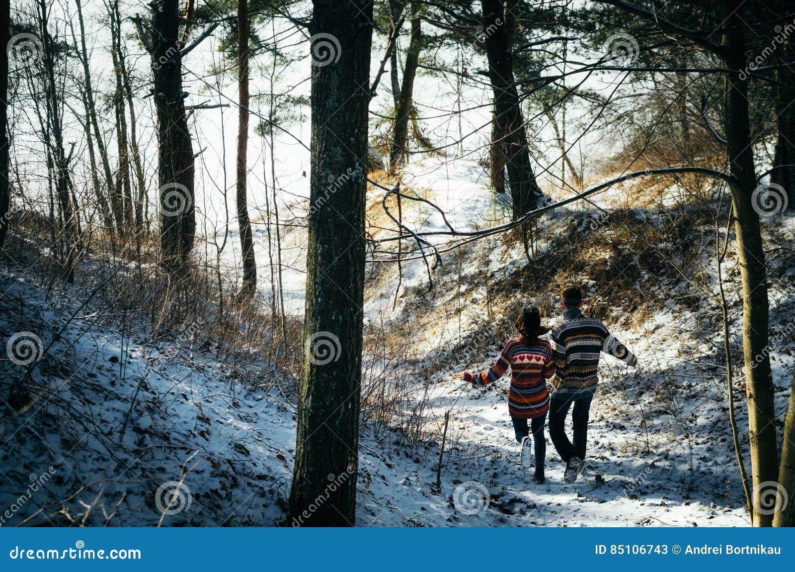 Los pares que llevan a cabo las manos corren lejos al bosque