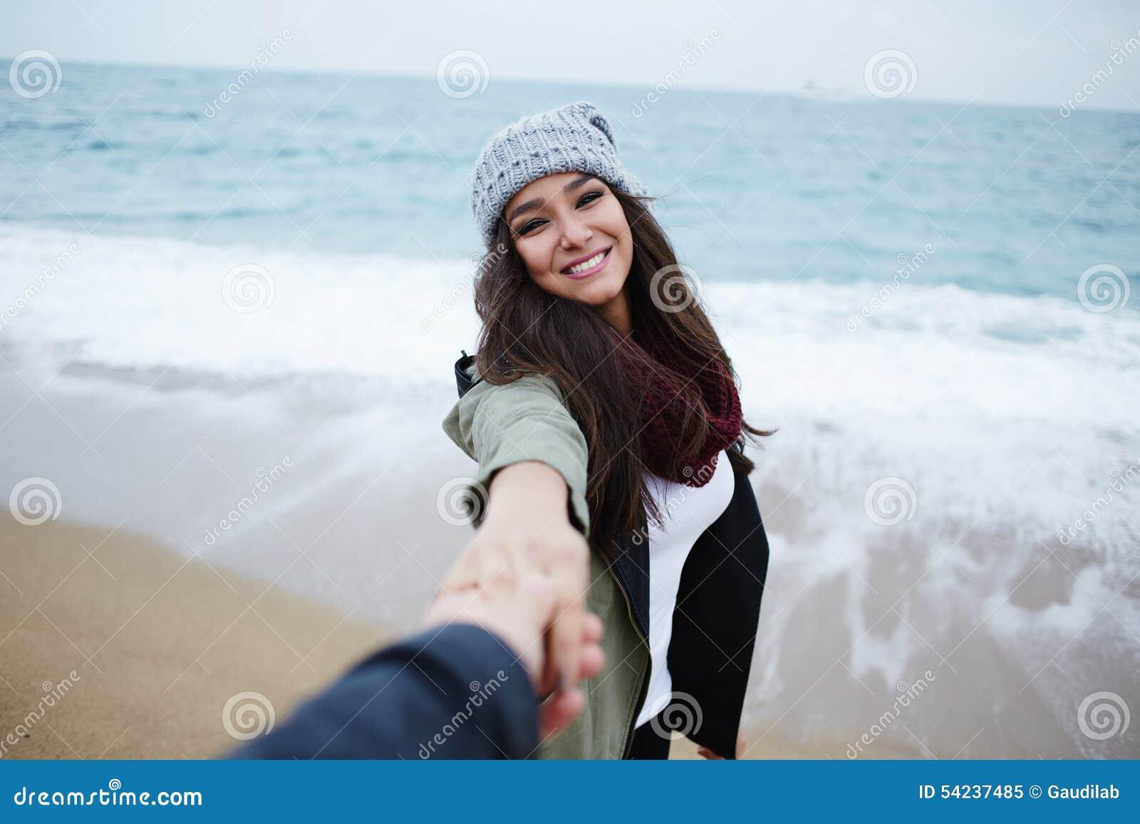 Los pares románticos en el paseo en la playa durante vacaciones viajan