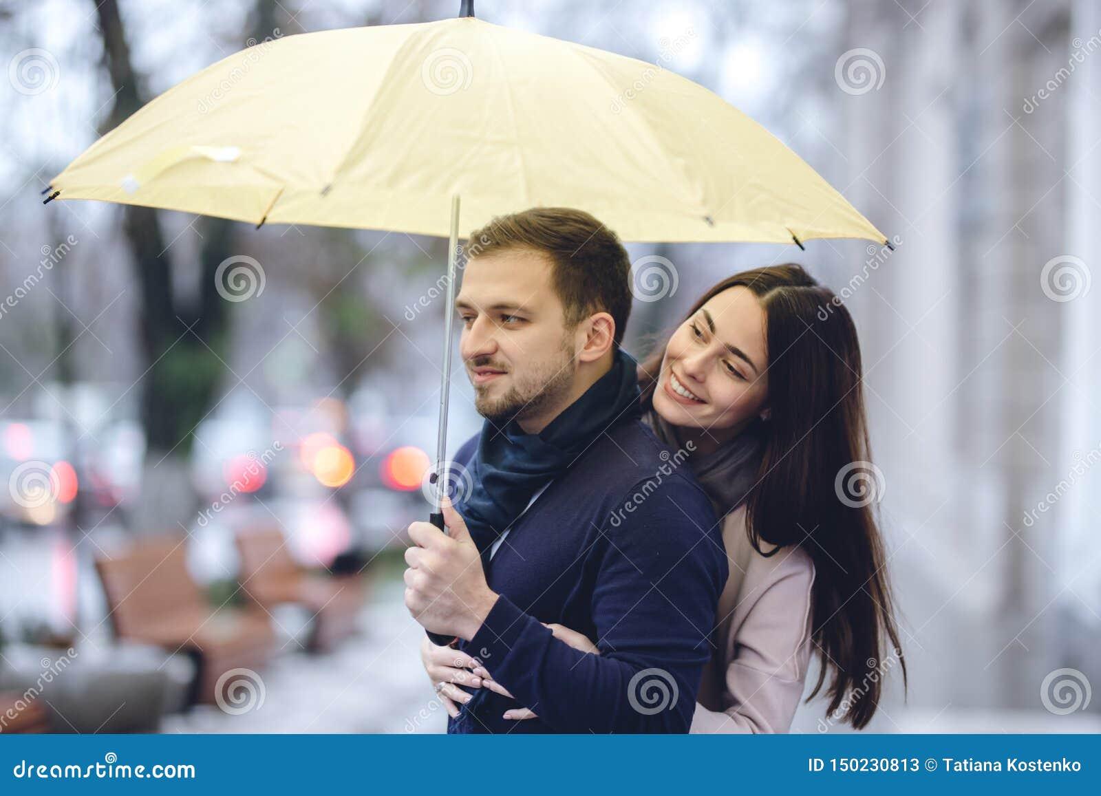Los pares rom?nticos felices, el individuo y su novia vestidos en ropa casual est?n abrazando debajo del paraguas y miran cada un