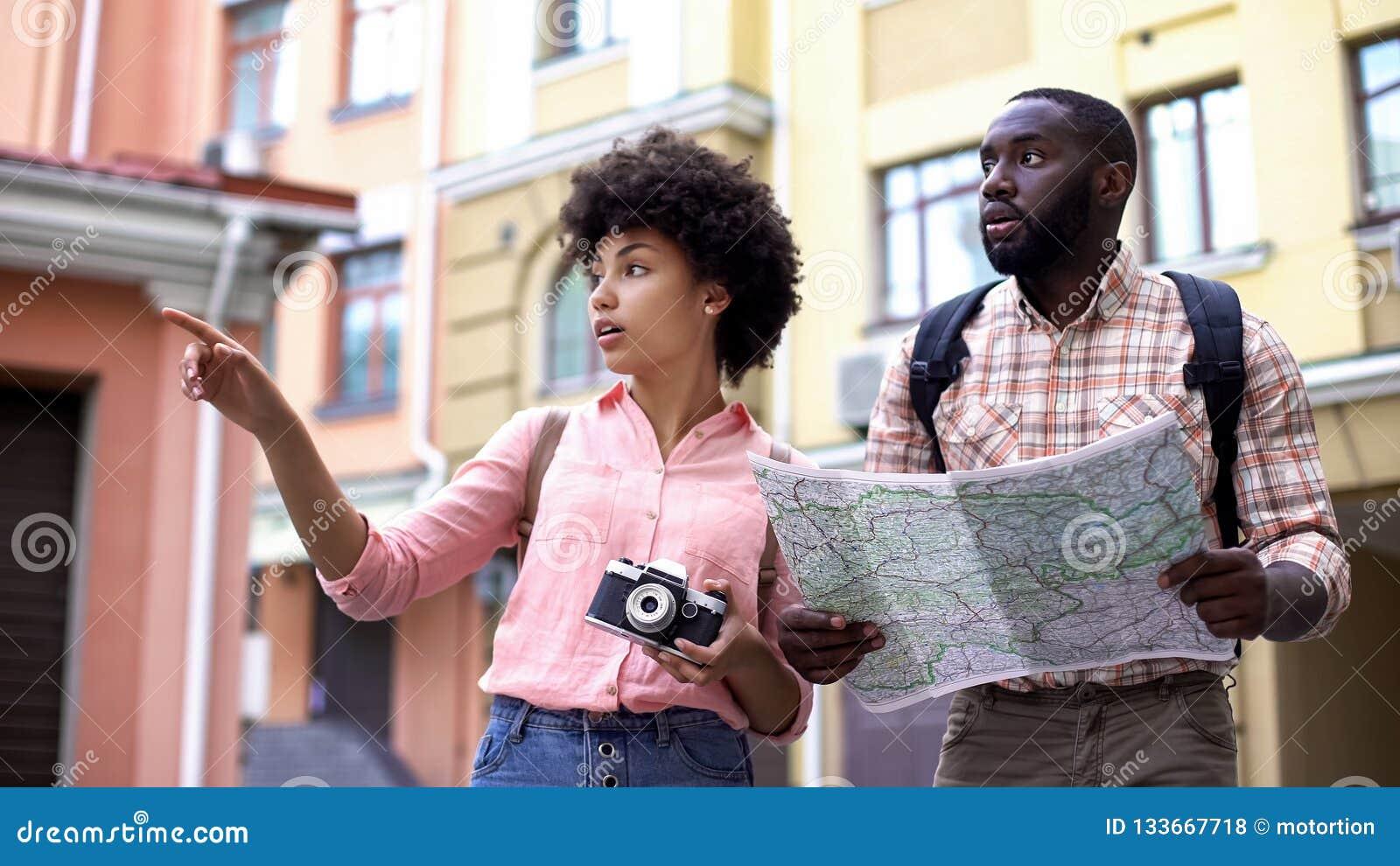 Los pares turísticos jovenes con la cámara del mapa y de la foto, eligiendo la dirección, viajan