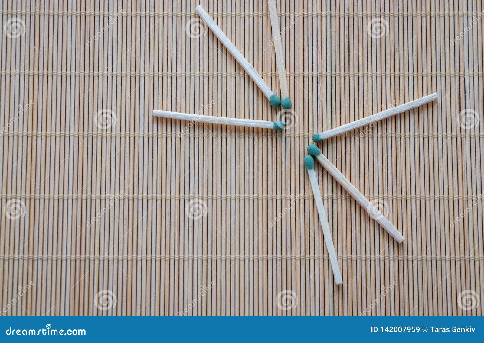 Los partidos de madera con las cabezas fosforadas verdes se dispersan en la tabla