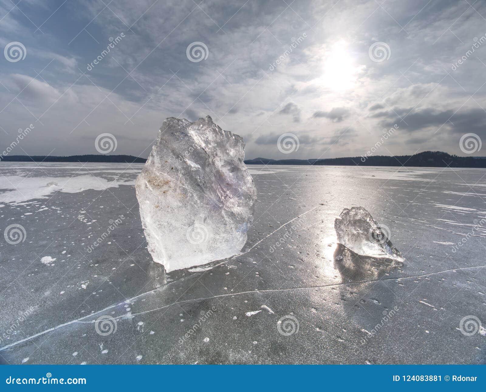 Los pedazos quebrados de hielo grueso sobre el lago congelado brillan en sol