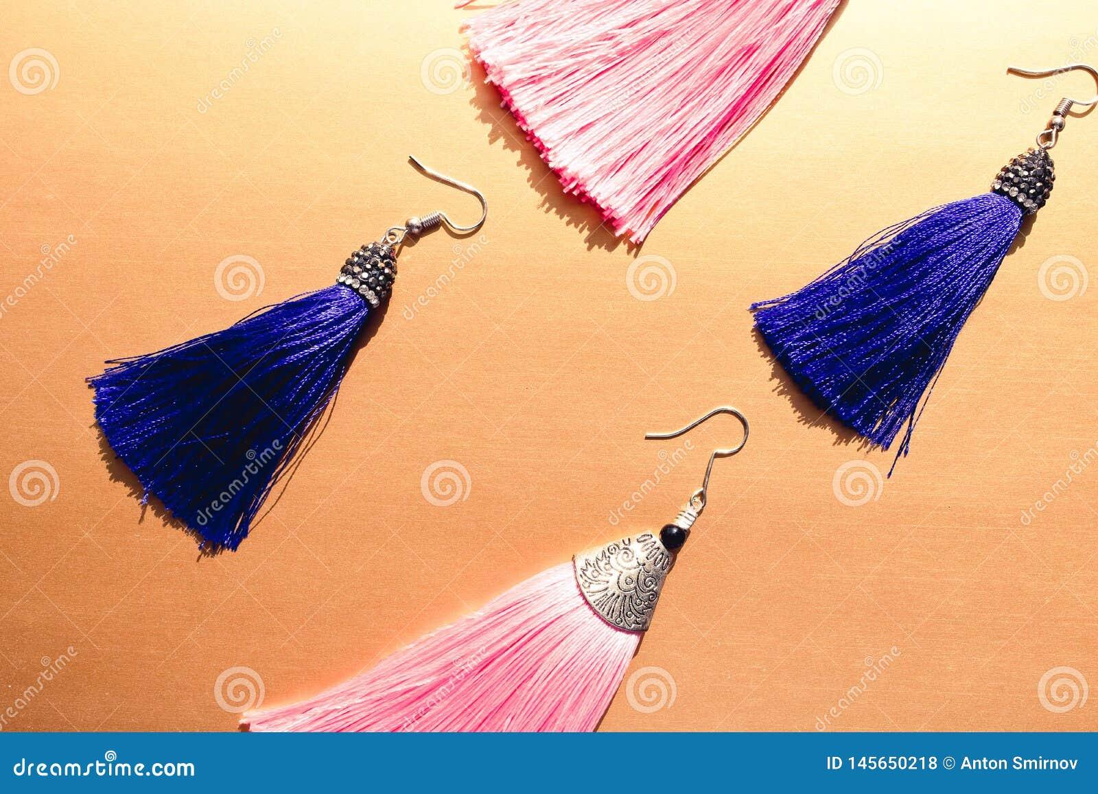 Los pendientes de la borla ven desde arriba Rosa y pendientes azul marino en fondo anaranjado