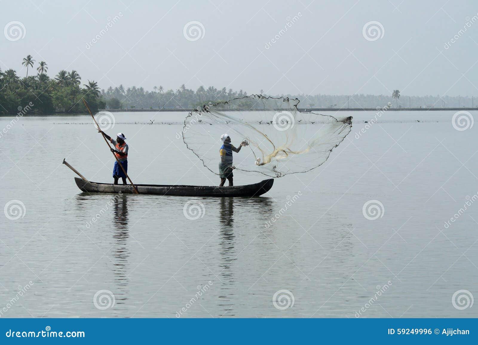 Los pescadores en un barco cogen pescados lanzando la red adentro a los remansos