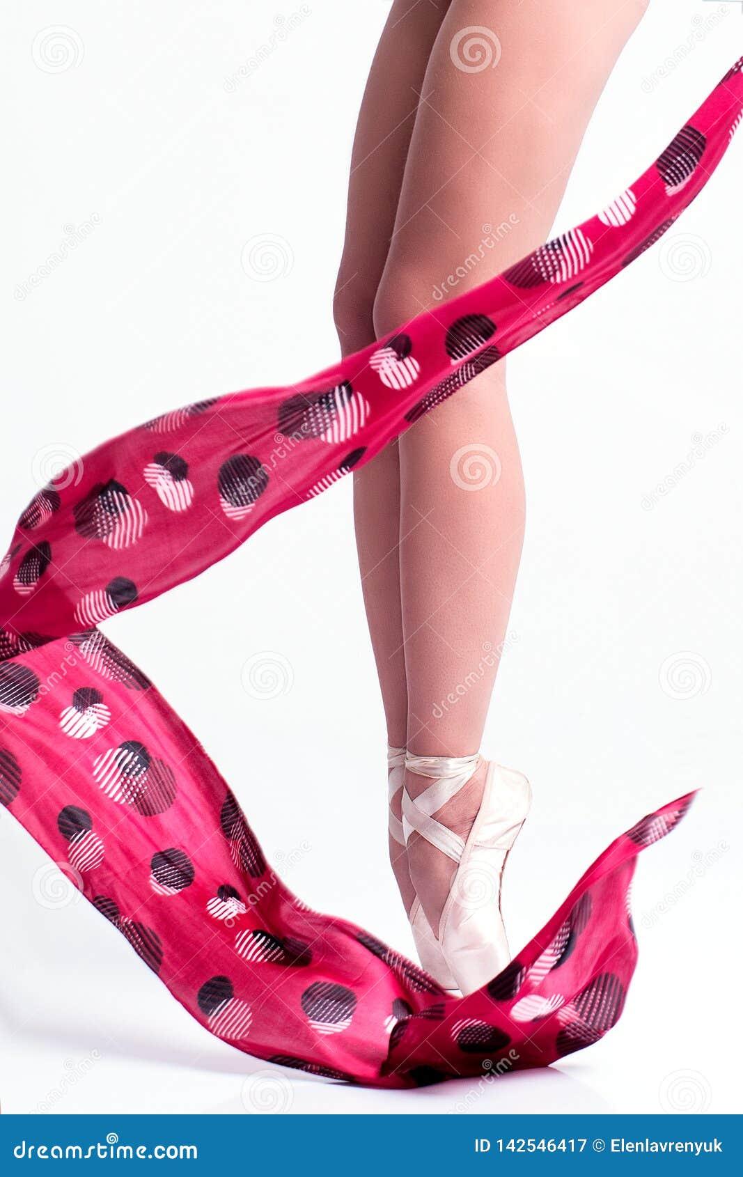 Los pies de la bailarina en pointe y con la cinta roja en el fondo blanco