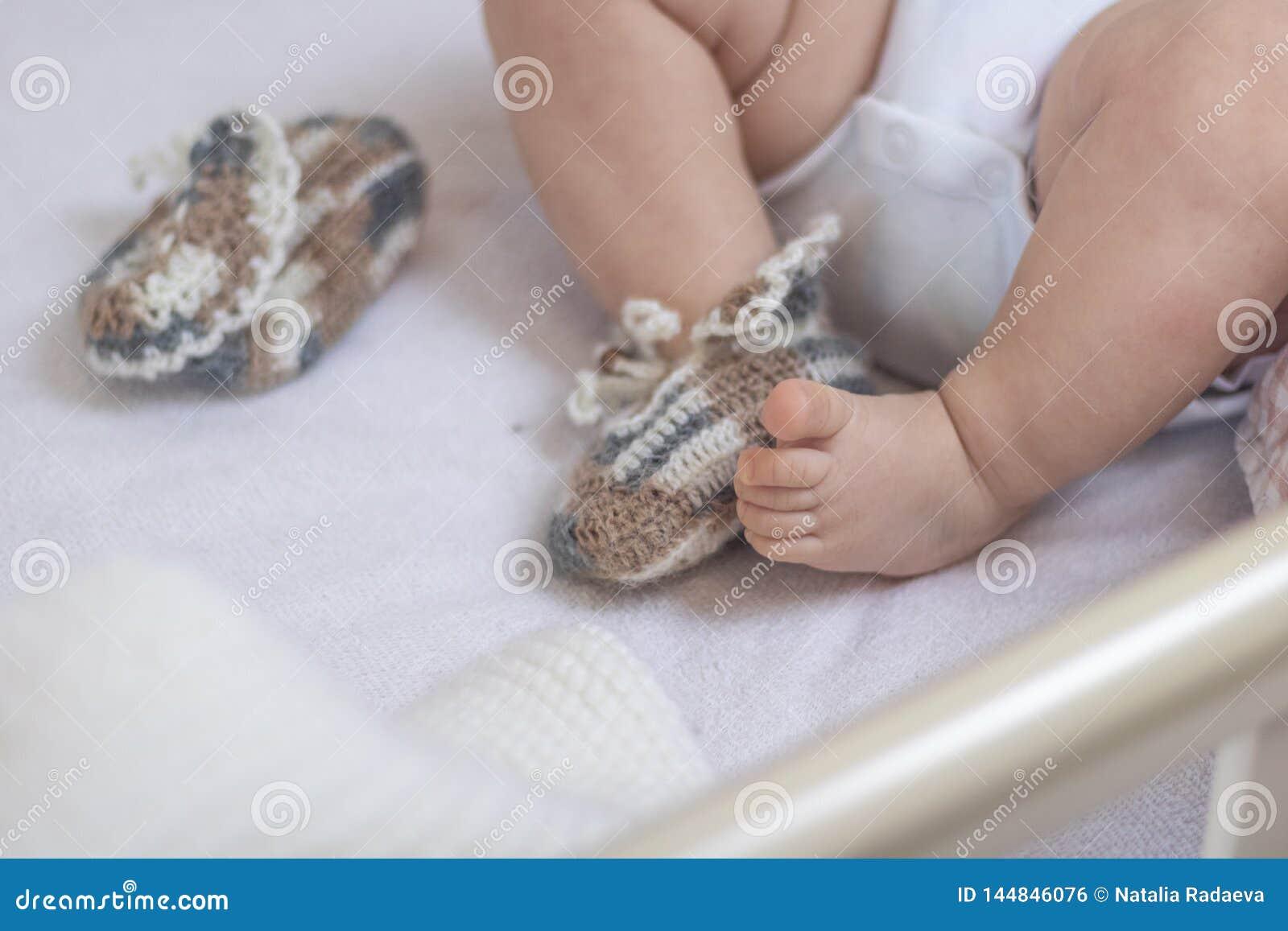 Los pies reci?n nacidos del beb? se cierran para arriba en calcetines de las lanas en una manta blanca El beb? est? en el pesebre